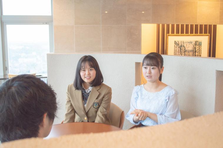 【写真】インタビューに真剣な表情で答える姉のまりあさんと、笑顔で聞いている妹のゆりあさん