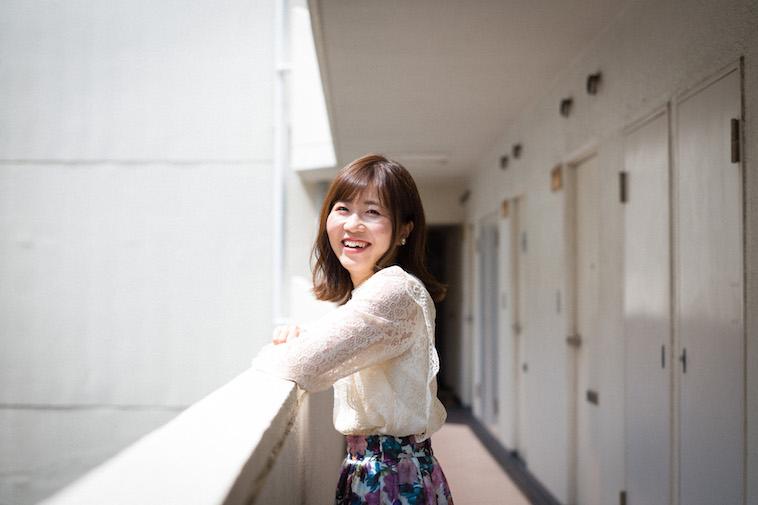【写真】マンションの玄関前で笑顔をみせるすがわらちかさん
