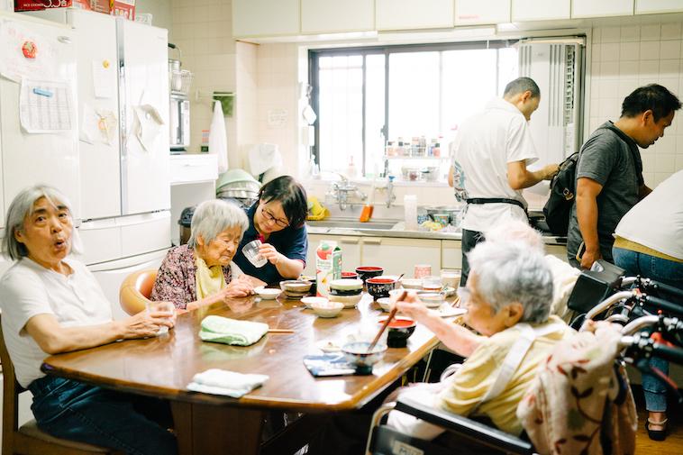 【写真】食卓で、利用者に食事の介助をするスタッフのみなさん