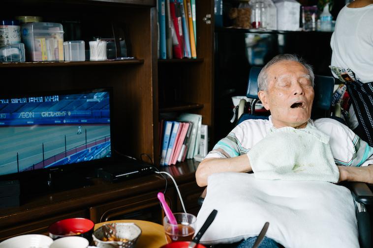 【写真】テレビの前で心地よさそうに目をつぶっているおじいさん