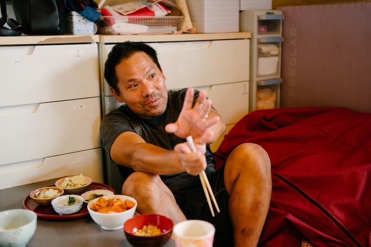 【写真】ご飯を食べながらインタビューに応えるいしいさん