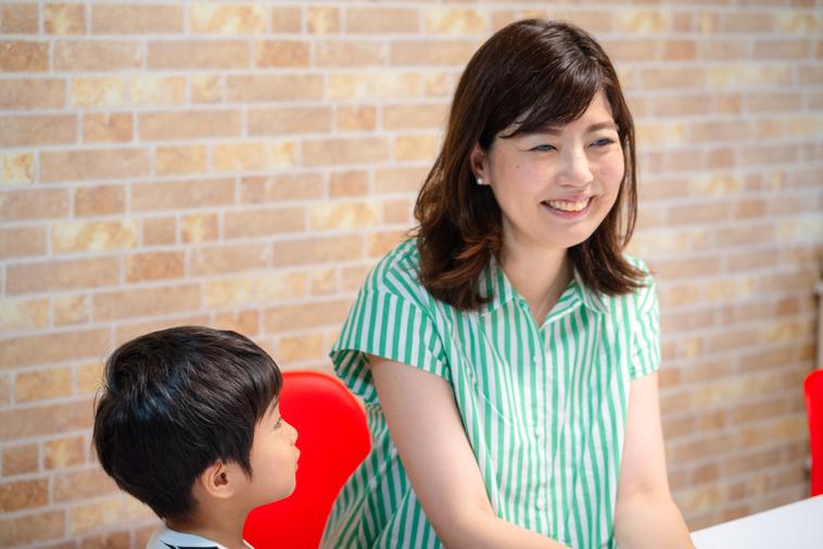 【写真】笑顔でインタビューに答えるいながきともいさん。横にはいながきさんをみつめるお子さんがいる。