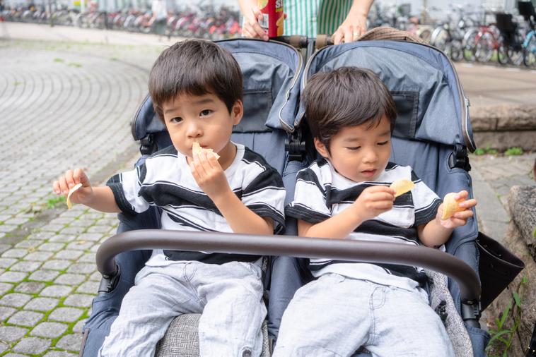 【写真】双子用ベビーカーにのって、お菓子をたべているいながきさんの二人の子供たち