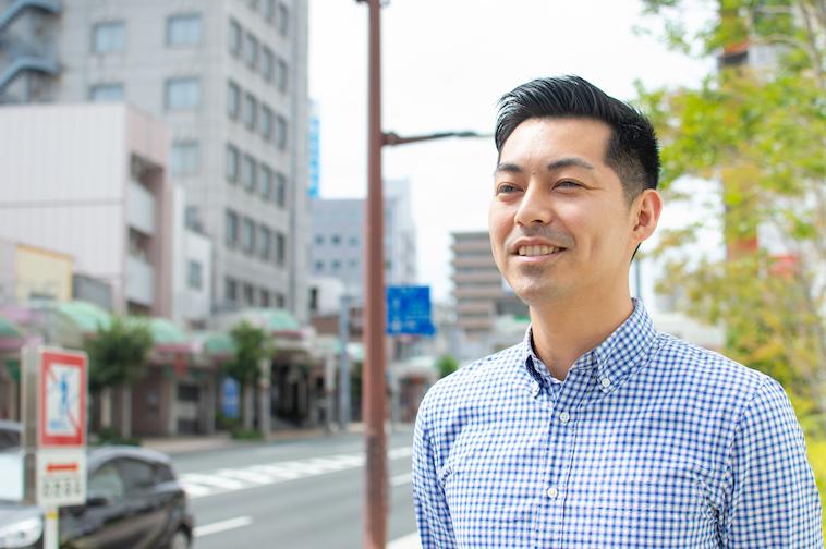 【写真】街頭で微笑みながら立っているなかむらしんじさん