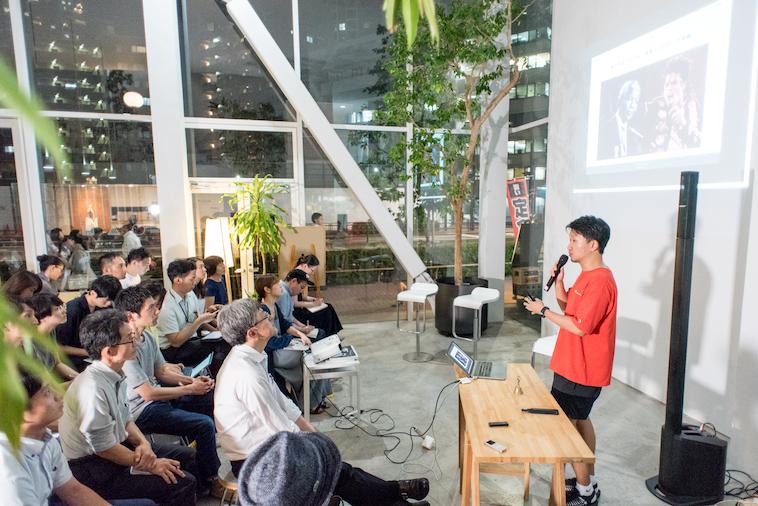 【写真】満員の会場で話すおおたなおきさん。参加者は真剣に話を聞いている。