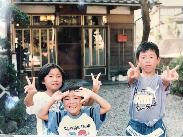 【写真】なかむらさんの幼少期の写真。ポーズをとっているなかむらさんの両隣には、ピースサインをみせているなかむらさんのお姉さん、お兄さんがいる。