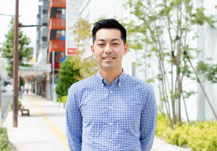 【写真】街頭で微笑んで立っているなかむらしんじさん