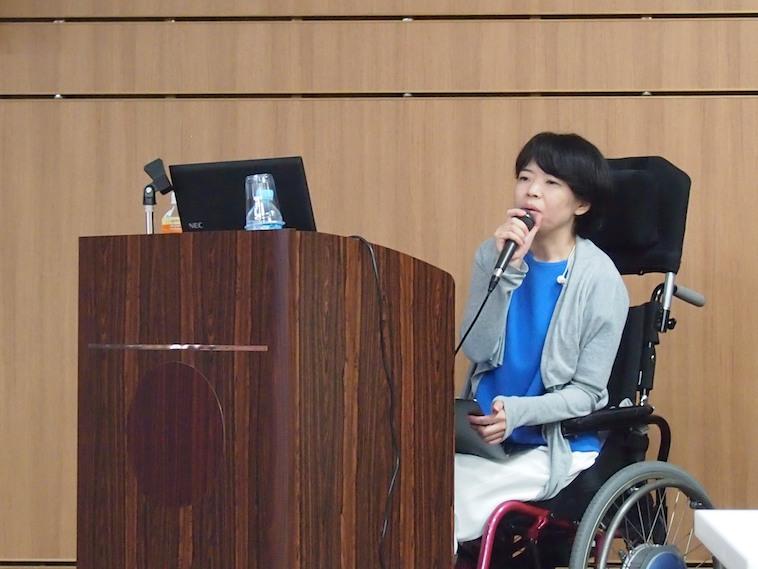 【写真】車椅子に座りながら真剣な表情で登壇しているさとうまゆこさん