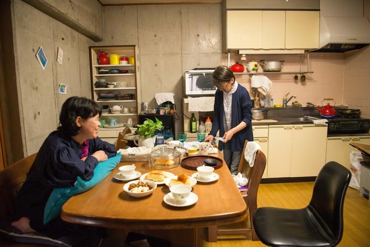 【写真】お茶を準備するまゆこさんのお母さんと、笑って見守るさとうまゆこさん。二人の間に穏やかな空気が流れている。
