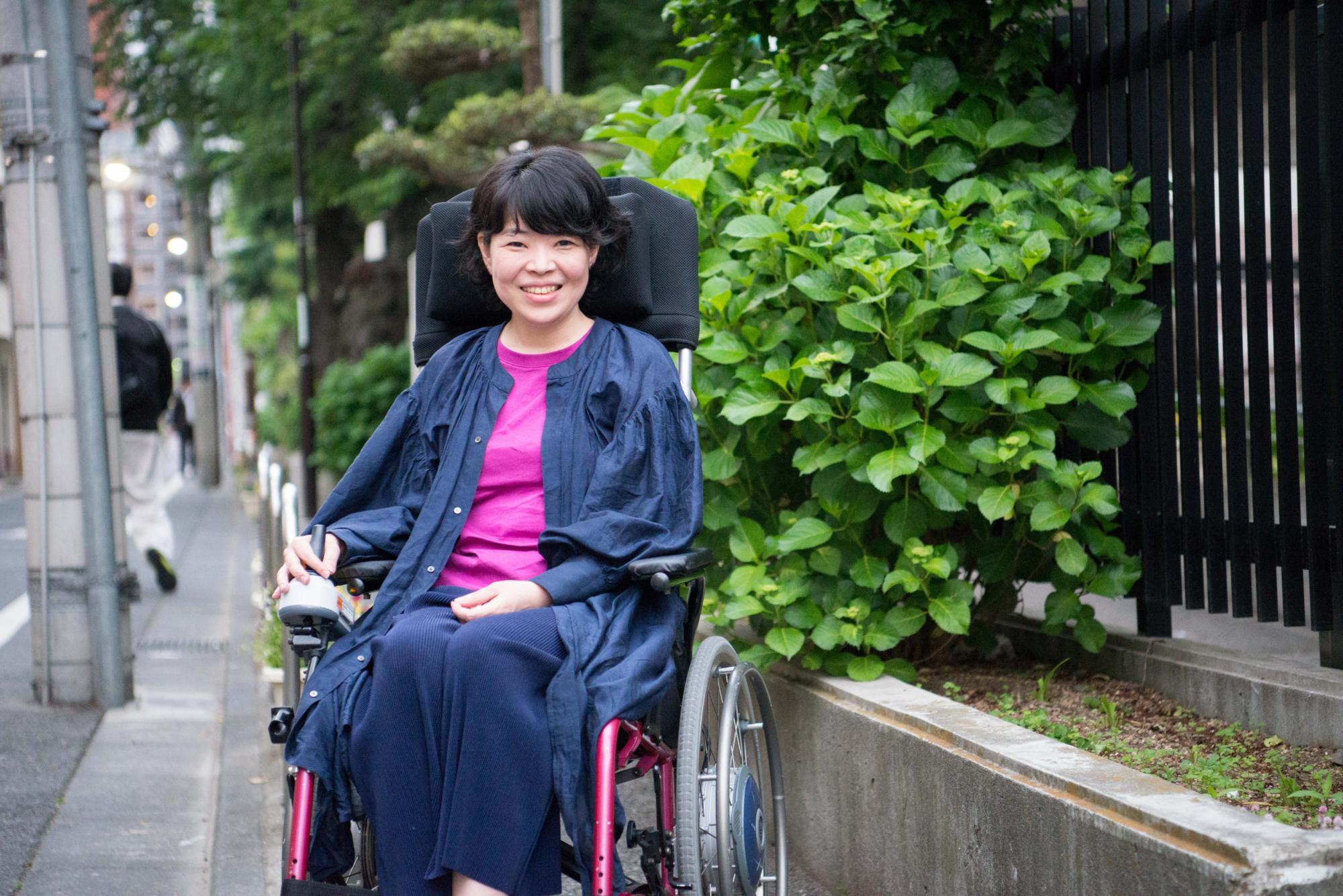 【写真】街頭で車椅子に座り笑顔のさとうまゆこさん