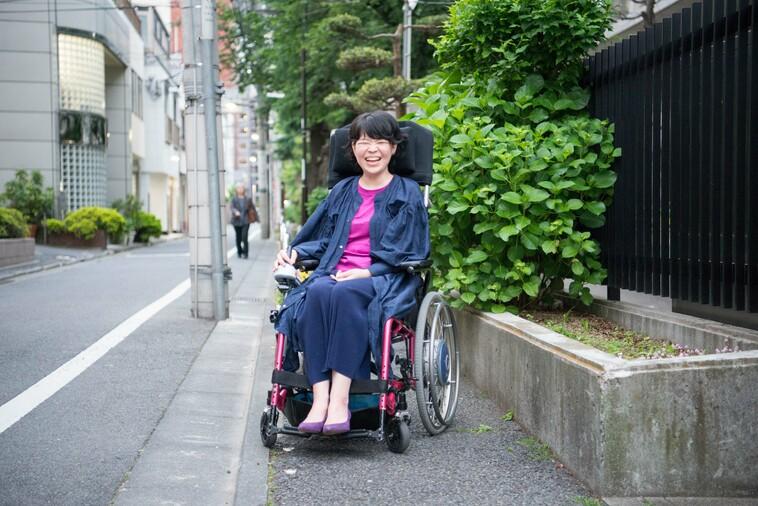 【写真】街頭で車椅子に座り満面の笑みをうかべるさとうまゆこさん