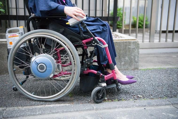 【写真】街頭を車椅子で移動するさとうまゆこさん