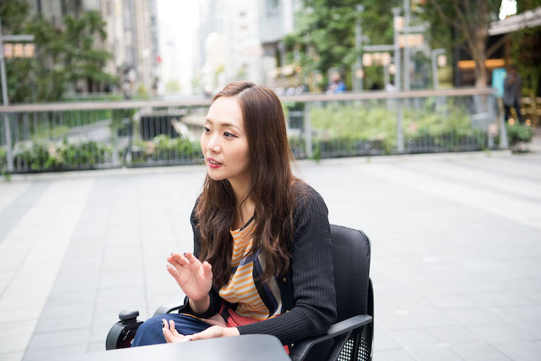 【写真】街頭で車椅子に座り真剣な表情でインタビューに答えるみおしんさん