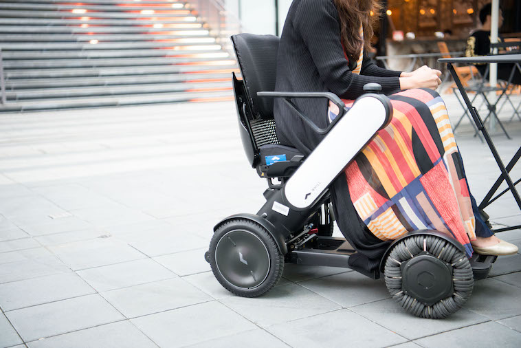 【写真】街頭で車椅子に座るみおしんさん。車椅子にはうぃると書かれている。