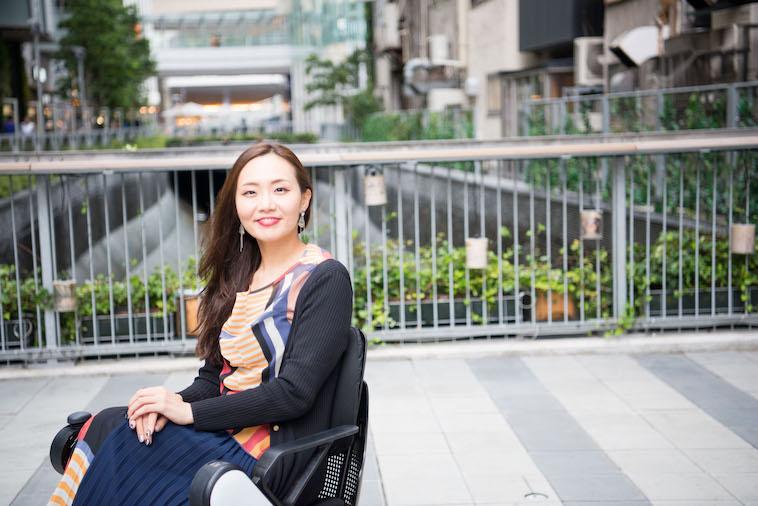 【写真】街頭で車椅子に座り、微笑むみおしんさん