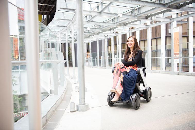 【写真】街頭で車椅子に座り満面の笑みを浮かべるみおしんさん