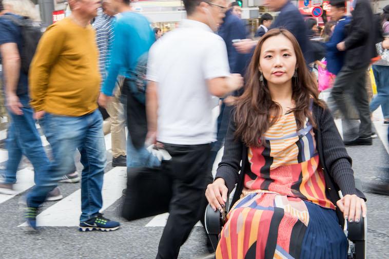 【写真】街頭で車椅子に座るみおしんさん。後ろには多くの人々が行き交っている。