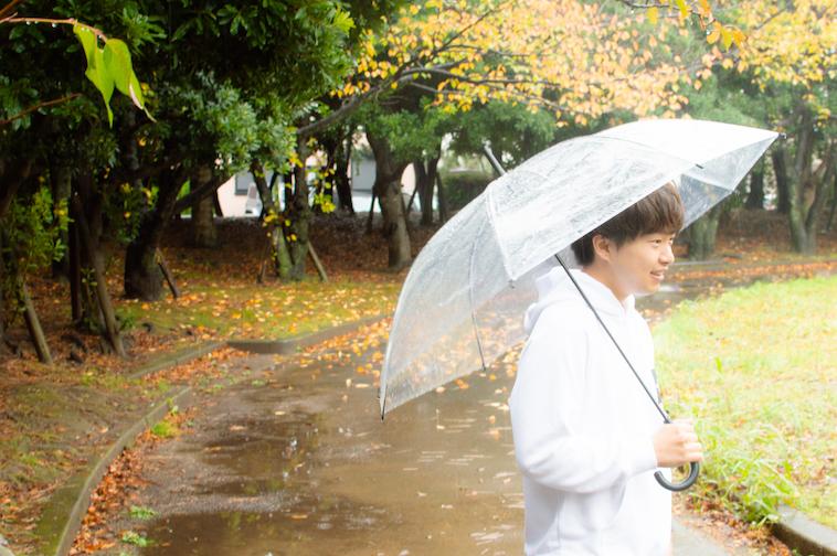 【写真】外で、傘をさしながら話すかわさきすぐるさん