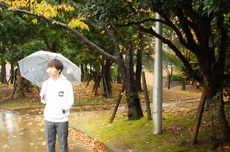 【写真】傘をさしながら、どこかをみつめているかわさきすぐるさん