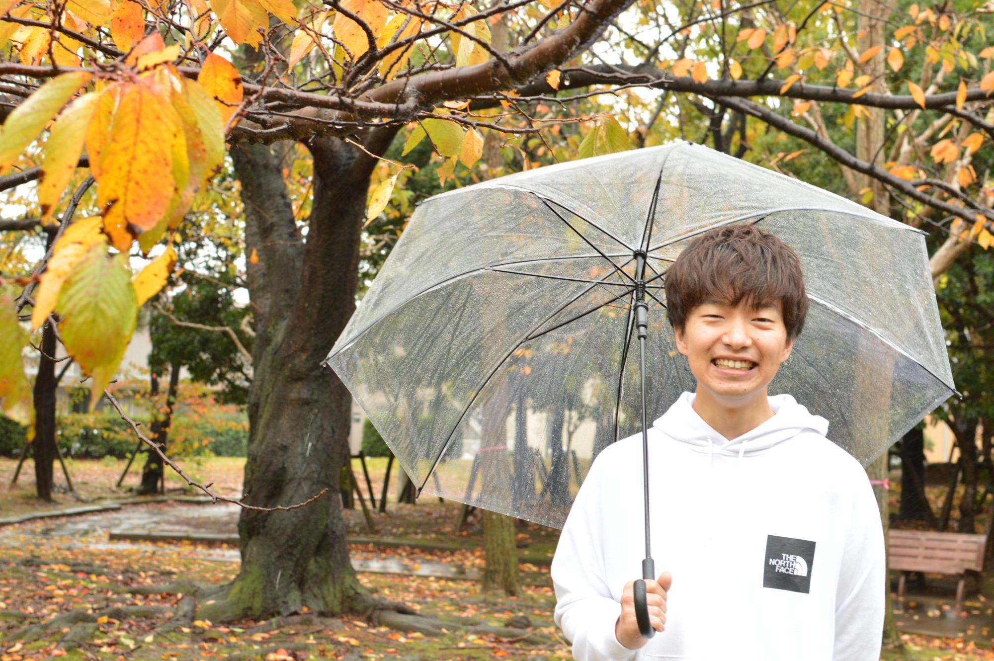 【写真】雨が降っている中、傘をさして笑顔のかわさきすぐるさん