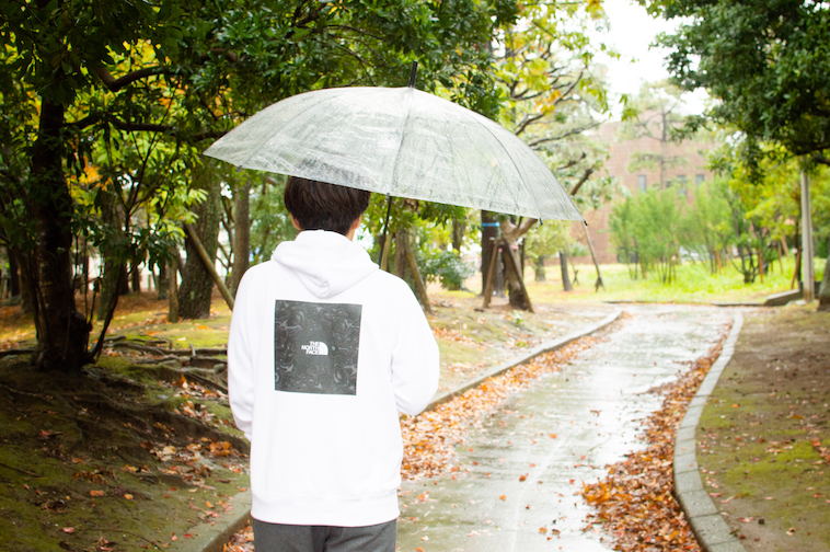 【写真】傘をさしながら公園を歩くかわさきすぐるさんの後ろ姿