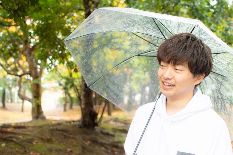 【写真】公園で傘をさしながら笑顔のかわさきすぐるさん
