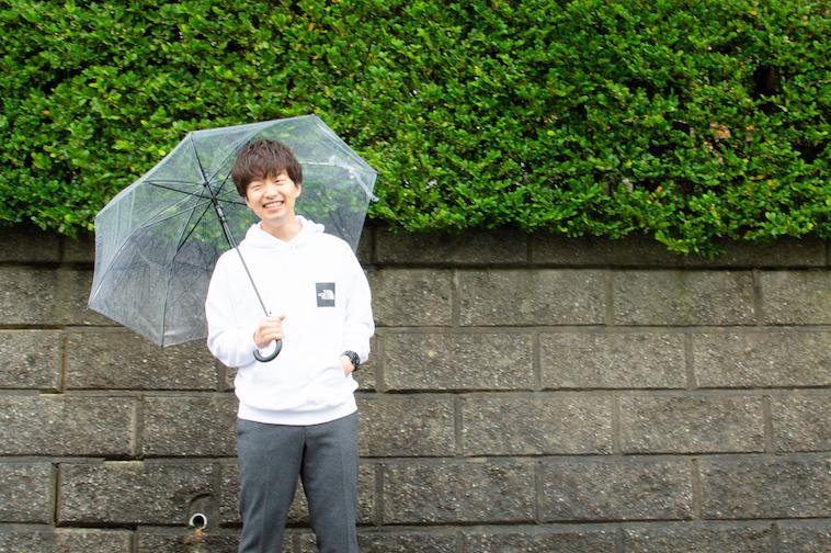 【写真】石垣の前で、笑顔で立っているかわさきすぐるさん
