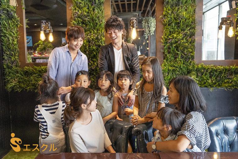 【写真】カフェで交流する親御さんと子どもたち。お互いの顔を見つめ合い笑っている。