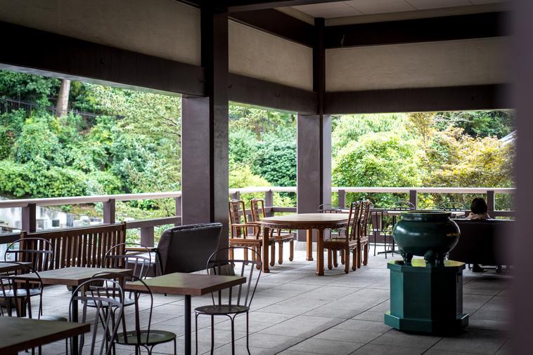 【写真】光明寺の一角。木製の椅子や机があり、木の柵の外側には森がある。