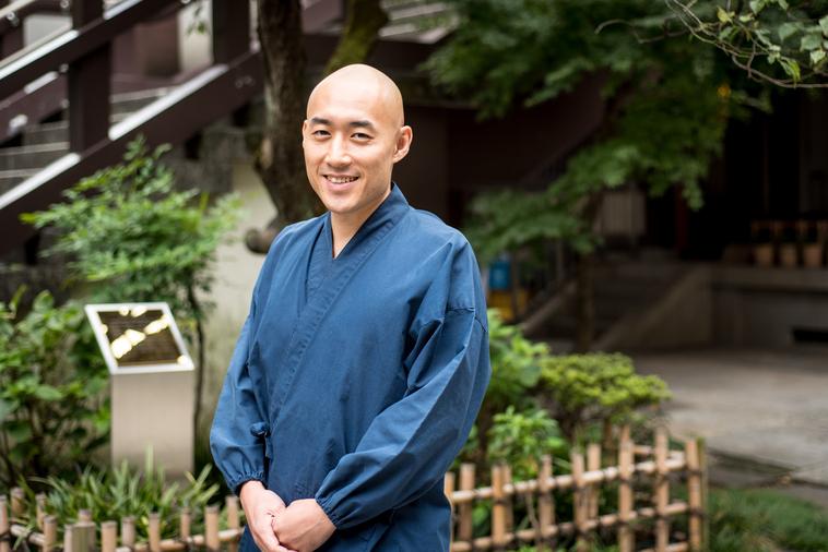 【写真】光明寺の前で立っている笑顔のまつもとしょうけいさん