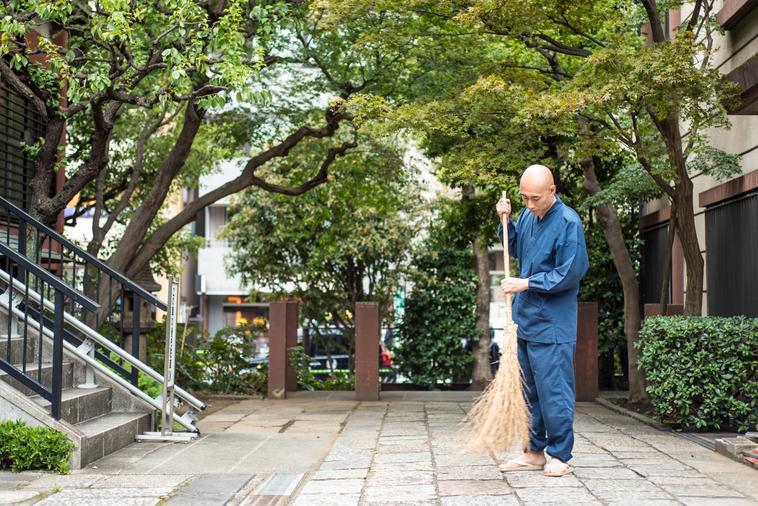 【写真】光明寺の入り口を竹ぼうきで掃いているまつもとしょうけいさん