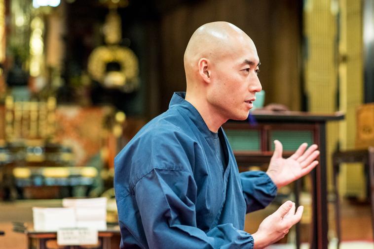 【写真】光明寺の本堂で真剣な表情でインタビューに答えるまつもとしょうけいさん
