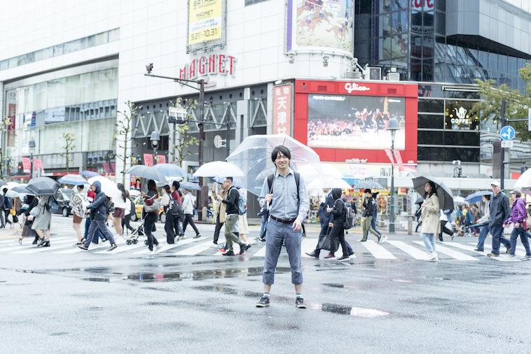 【写真】渋谷のスクランブル交差点の前で立ついまいさん。笑顔でこちらをみている。