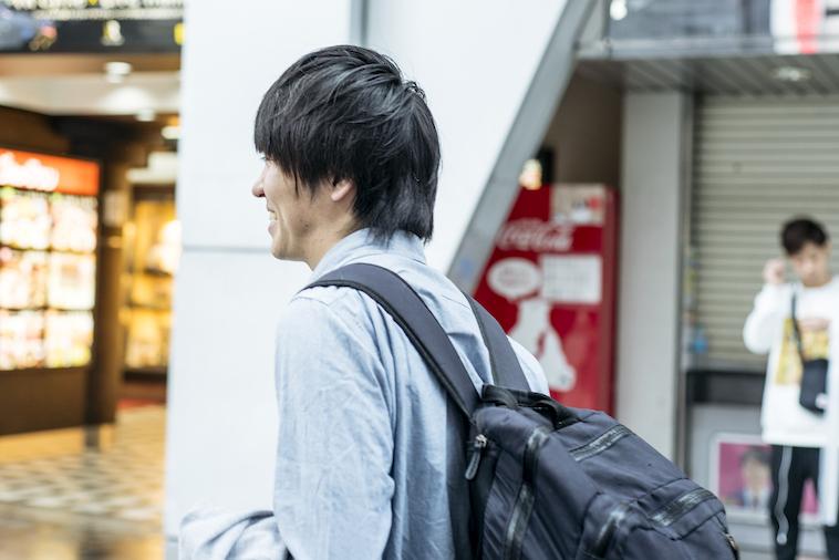 【写真】屋外を歩くいまいさんの横顔。笑みを浮かべている。