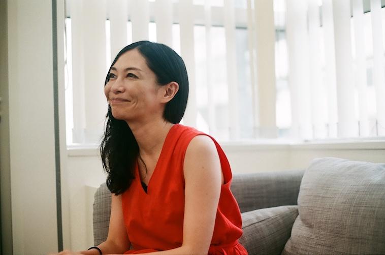 【写真】椅子に座って微笑む小澤さんの横顔