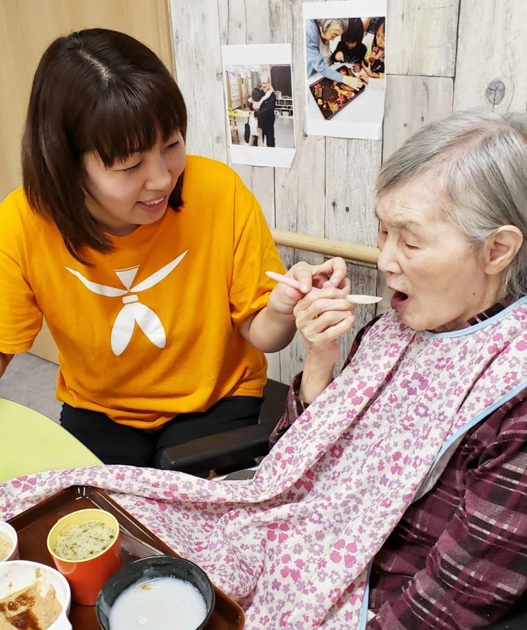 【写真】あづみさんが高齢者の女性の食事のサポートをしている様子