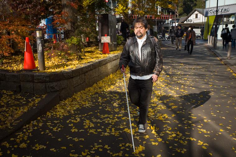 【写真】白杖を持って歩道を一人で歩いている中根さん