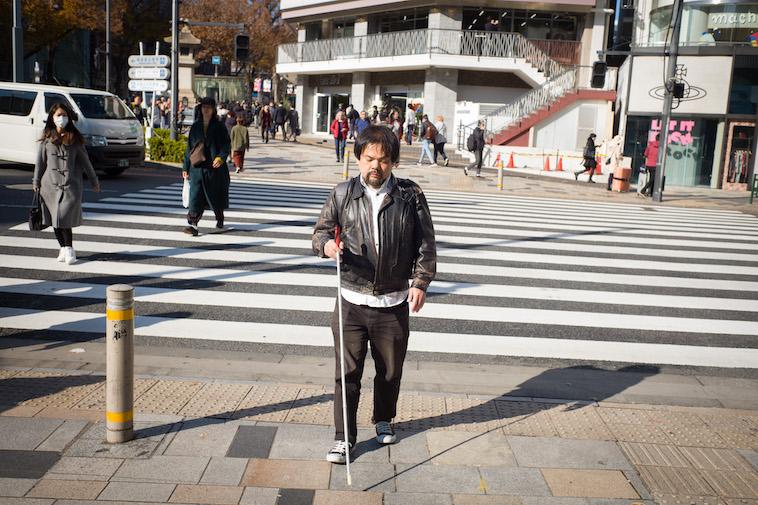 【写真】白杖を持って道路を歩いている中根さん