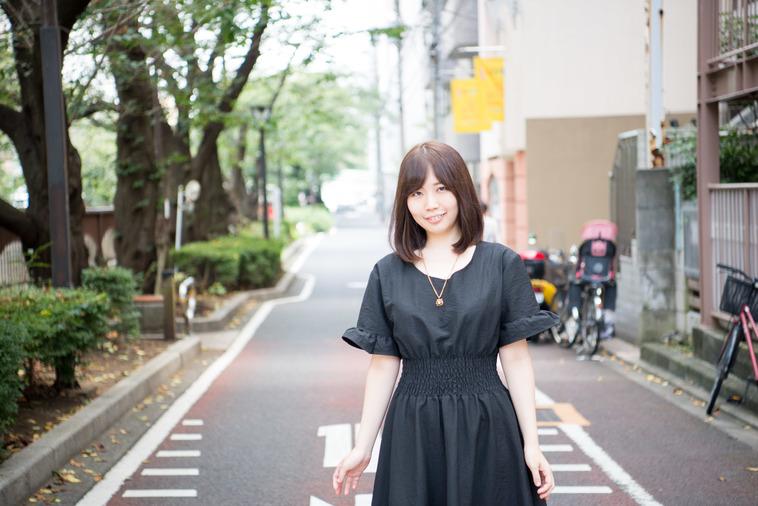 【写真】道路を歩きながらこちらに微笑むしみずさん