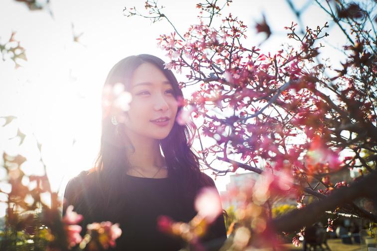 【写真】梅の花の前で微笑むまりこさん
