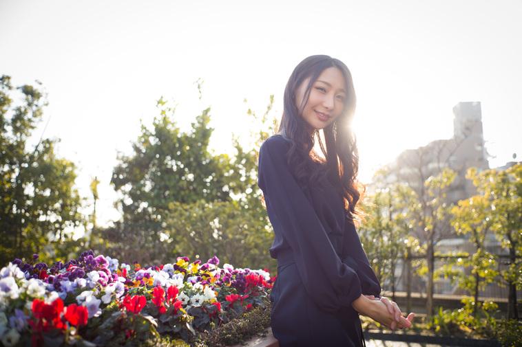【写真】花壇の前で微笑むまりこさん