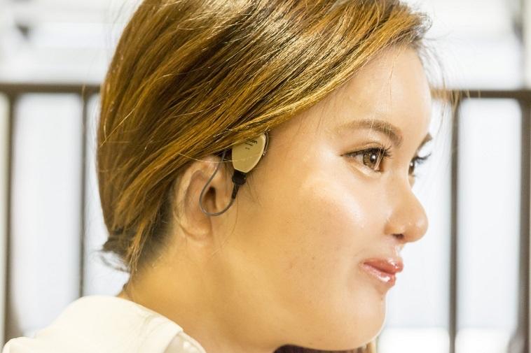 【写真】耳の上に骨伝導補聴器をつけているこばやしさん