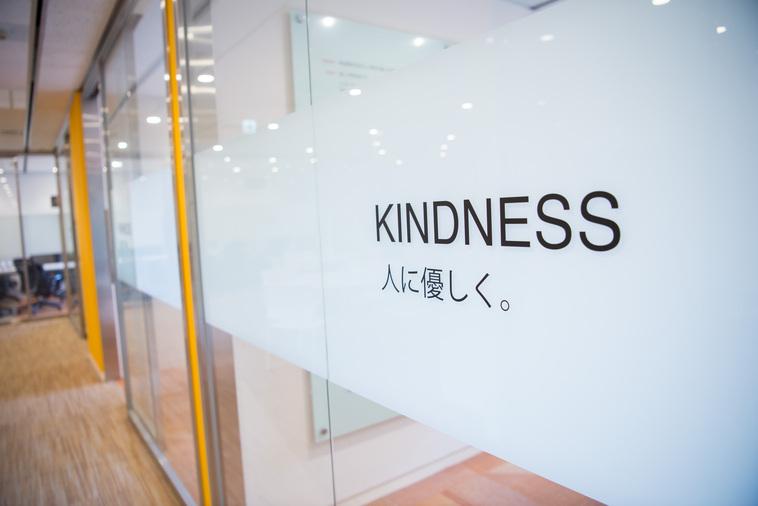 【写真】CAMPFIREのオフィスの壁には「KINDNESS人に優しく。」と書かれている