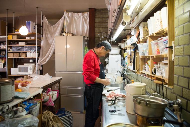 【写真】台所で料理をするしげさん。