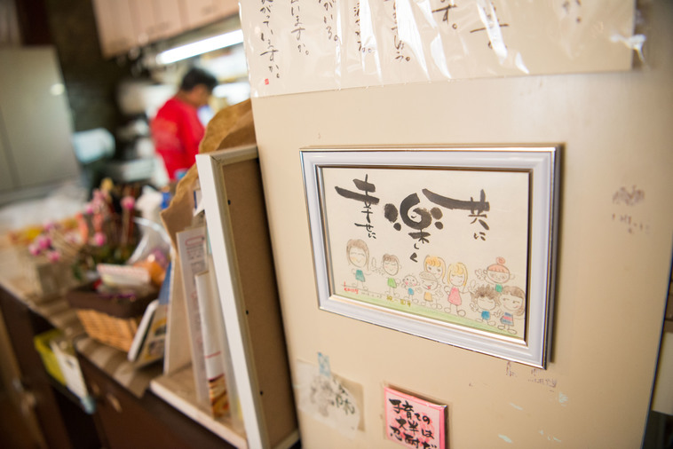 【写真】まなはうすの理念である「共に楽しく幸せに」の文字と一緒にたくさんのお母さんや子供が一緒にる絵が描かれている