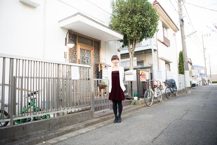 【写真】まなはうすの玄関前で笑顔で立っているやまなかさん
