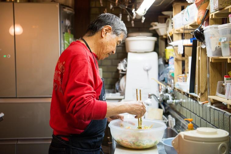 【写真】台所でシゲさんがサラダを作っている
