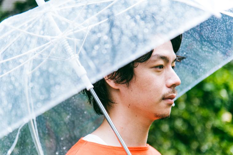 【写真】傘をさし、遠くを眺めるみやざきさん