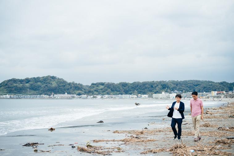 【写真】海岸を歩くかとうてつおさんとすずきゆうへい