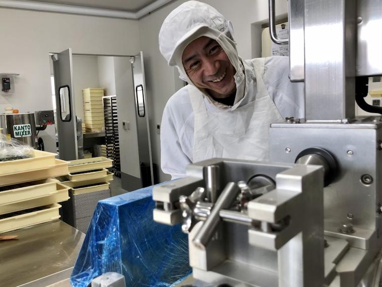 【写真】製造機のうしろからこちらを見て微笑むタカヨシさん